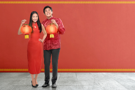 Young chinese couple with traditional dress holding red lanterns on red wall background. Happy Chinese New Year