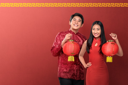 Beautiful chinese couple holding red lanterns on red background. Happy Chinese New Year Stock Photo