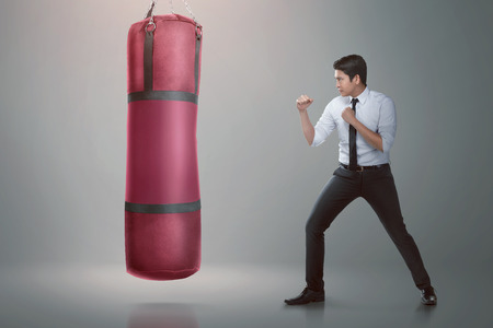 Young asian businessman punching boxing bag over gray background Banque d'images