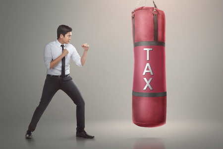 Handsome asian businessman ready to punch boxing bag with tax text on it. Taxation concept