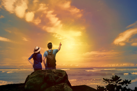 Lovely asian couple looking at sunset panorama from the beach  Archivio Fotografico