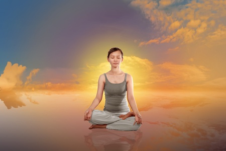 Young asian woman doing yoga with dramatic sunset background