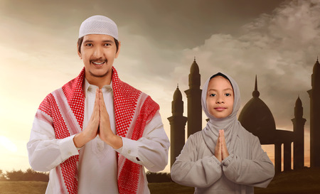 Religious asian muslim family with traditional dress pray during sunset