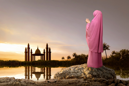 Rear view of asian muslim woman with headscarf praying during sunset background