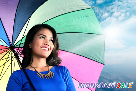 Smiling asian woman with umbrella. Monsoon sale concept