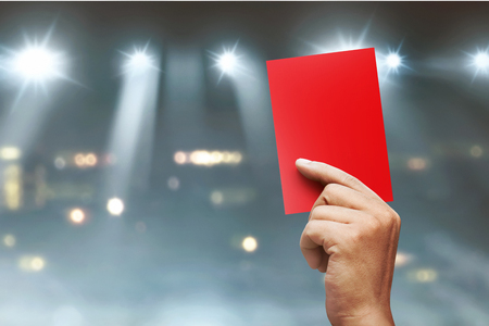 Referee hands showing red card on football match
