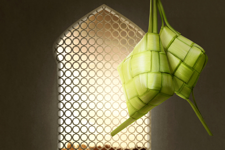 Ketupat or rice dumpling for Eid Mubarak with sunset view from windows