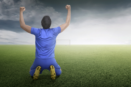 Back view of asian footballer man celebrate his goal on the field Stock Photo