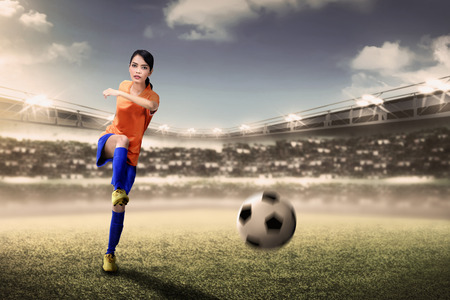 Attractive asian footballer woman kicking ball during match on stadium Standard-Bild