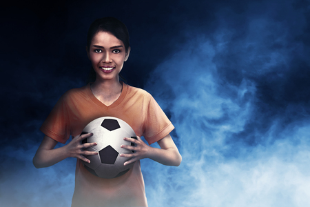 Smiling asian footballer woman carrying ball on her hand