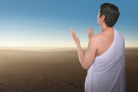 Religious asian hajj man praying with blue sky background
