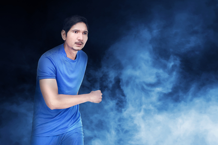 Handsome asian soccer player man with blue jersey over abstract background 스톡 콘텐츠