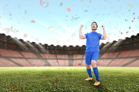 Attractive asian male football player celebrate victory in stadium