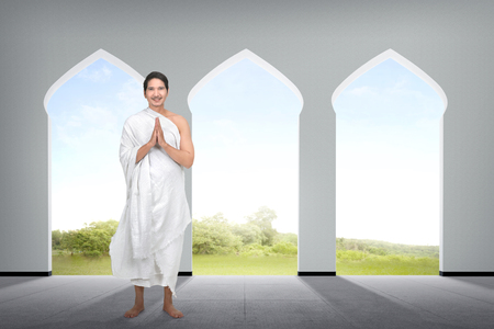 Religious asian muslim man with hand gesture on the mosque Stock Photo
