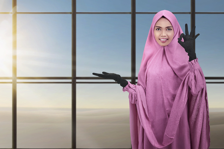 Beautiful asian muslim woman showing copyspace area with window glass background