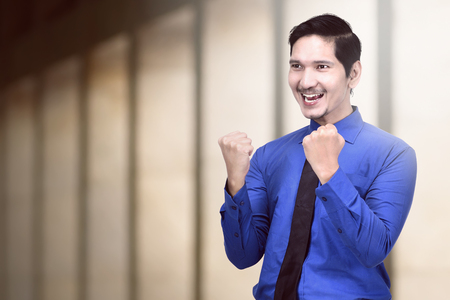 Young asian businessman celebrating his successfully on the office Stock Photo