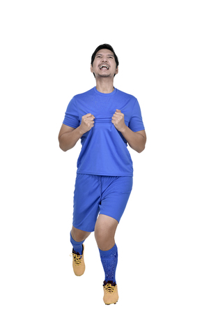 Happy asian football player man celebrate after scoring a goal isolated over white background