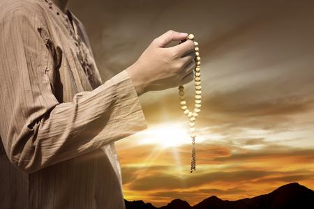 Muslim man praying with prayer beads during sunset background Stok Fotoğraf