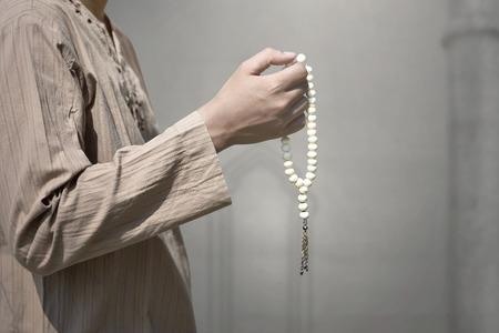 Muslim man praying with prayer beads inside the mosque