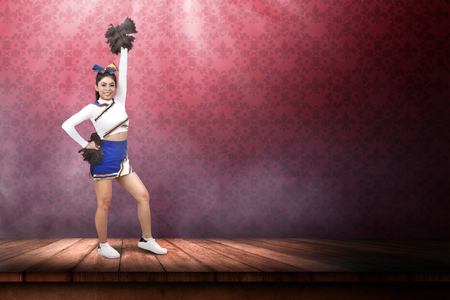 Beautiful asian cheerleader holding pom poms in her hands at stage
