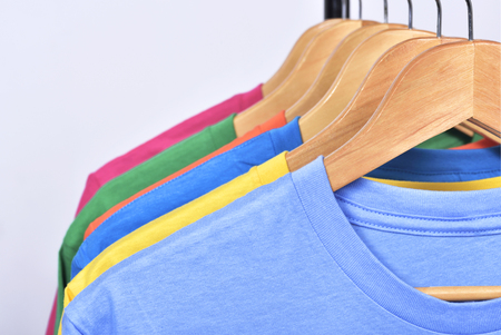 Colorful clothes hang on a shelf after washing isolated over white background