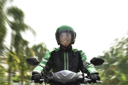 Asian motorcycle taxi rider rushing on the street