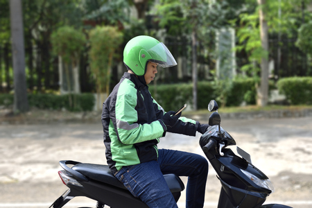 Side view of asian motorcycle taxi man checking the phone on the sidewalk Stockfoto