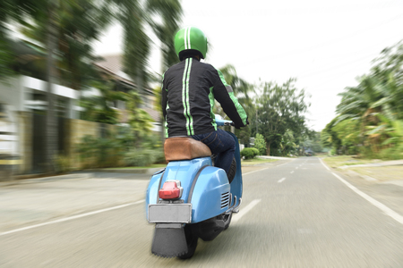 Back view of motorcycle taxi driver with blue scooter on urban street Stockfoto