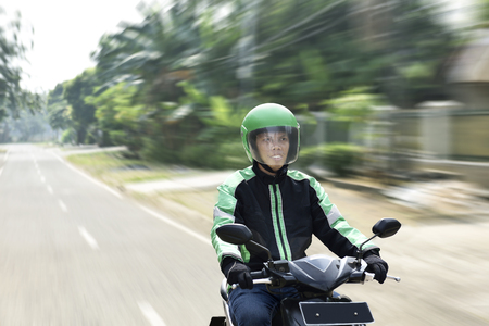 Young man working as motorcycle taxi driver on the urban street Stockfoto