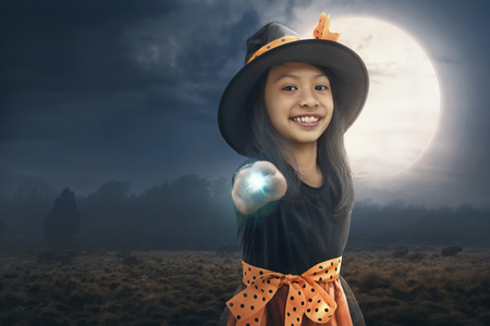 Smiling asian child girl using her magic power with moonlight background Фото со стока