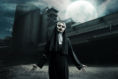 Scary asian devil nun standing on abandoned old factory at midnight Banque d'images