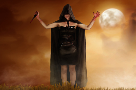 Young witch woman in black hooded cloak holding bloody knife with dramatic scene background