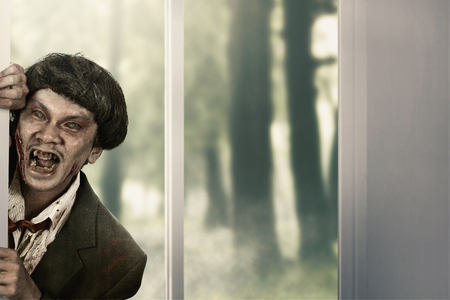 Creepy zombie man come into abandoned house. Halloween concept Banque d'images