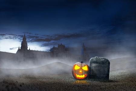 Glowing halloween pumpkin beside grave stones with old building background. Halloween background