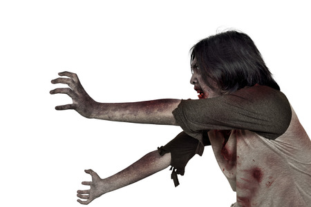 Side view of creepy zombie man with dirty hands standing isolated over white background 免版税图像
