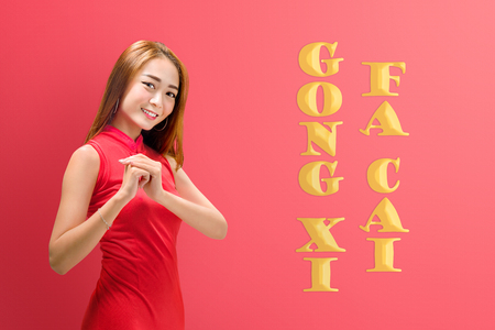 Pretty chinese woman in cheongsam dress wih gesture of congratulations. Happy Chinese New Year. Gong Xi Fa Cai