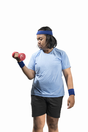 Attractive asian fat man working out with dumbbell posing isolated over white background. Fat man diet concept
