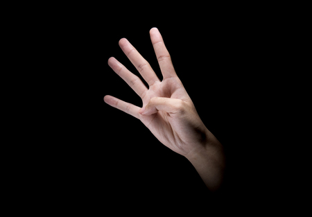 Male hands with four finger sign over dark background