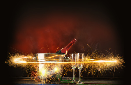 Champagne bottle in ice bucket with two of glasses and fireworks display on bright background Stockfoto