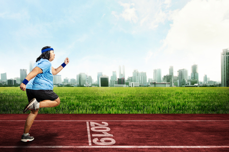 Asian fat man running on running track with 2019 number on the start line. New Year Resolution 2019