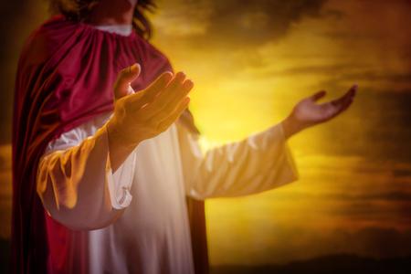 Jesus christ raising hands and praying with sunset background Stock Photo