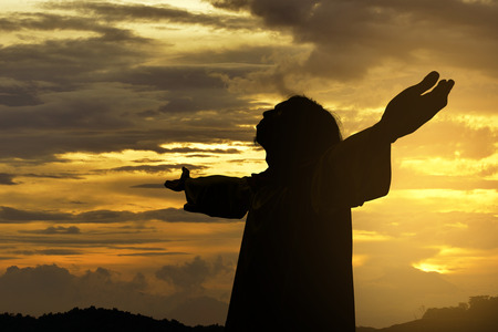 Silhouette of Jesus christ standing with raised arms at sunset background Stock Photo