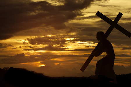 Silhouette of Jesus christ carrying cross over sunset background