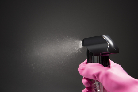 Hand in gloves using spray bottle with spraying water into the air over black background