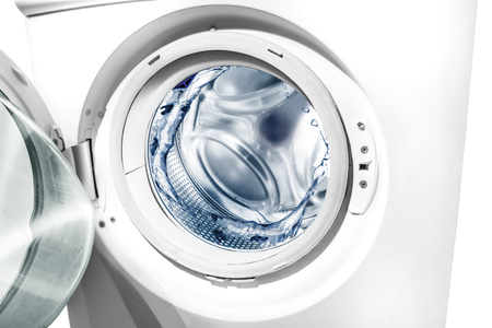 Water splashes in washing machine drum over white background