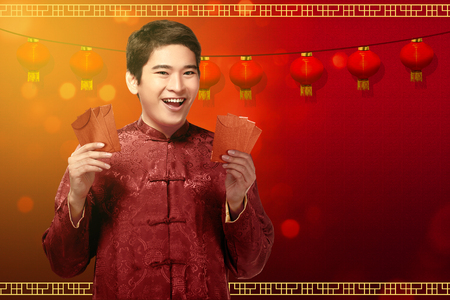 Attractive chinese man in traditional clothes showing angpao on his hands. Happy Chinese New Year