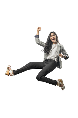 Successful asian business woman jumping and raised arm to the air posing isolated over white background