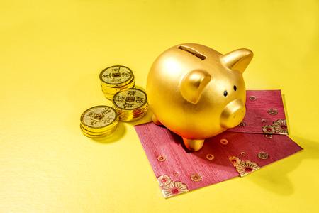 Sparschwein mit goldenen Münzen und roten Umschlägen auf gelbem Hintergrund. Chinesisches Neujahr. Jahr des Erdschweins