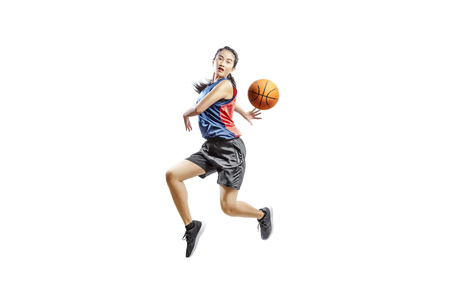 Pretty asian woman playing basketball posing isolated over white background Foto de archivo