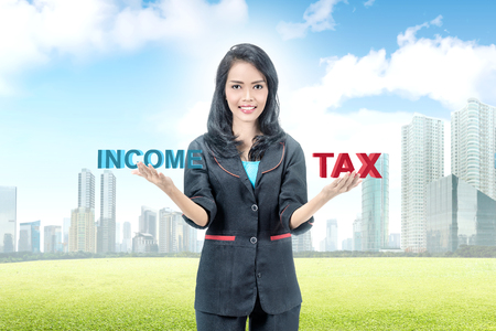 Young asian businesswoman balancing between income and tax. Taxes concept Imagens